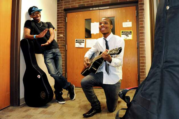 Resaan Bowman, also known as Kidd Casanova, 20, left, claps along as fellow music student Greg Henderson, 18, does an improve performance during the opening of the new Music School on Wednesday, Sept. 12, 2012, at Schenectady County Community College in Schenectady, N.Y. Henderson joined The Litches and will be playing different genres of rock locally. Bowman is a rapper for an independent label. (Cindy Schultz / Times Union) Photo: Cindy Schultz / 00019226A