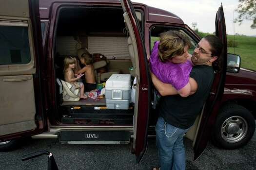 After a long day of driving, the Hayes family stops for the night at a motel in Natural Bridge, Virginia, July 8, 2012. Al Hayes lifts his wife Katy Hayes out of the family van as their kids, two year-old Arielle and eight year-old Jake, pack up there belongings. Katy Hayes and family are moving to Boston, Mass. to be closer to Brigham and Women's Hospital. Photo: Billy Smith II, Chronicle / © 2012 Houston Chronicle