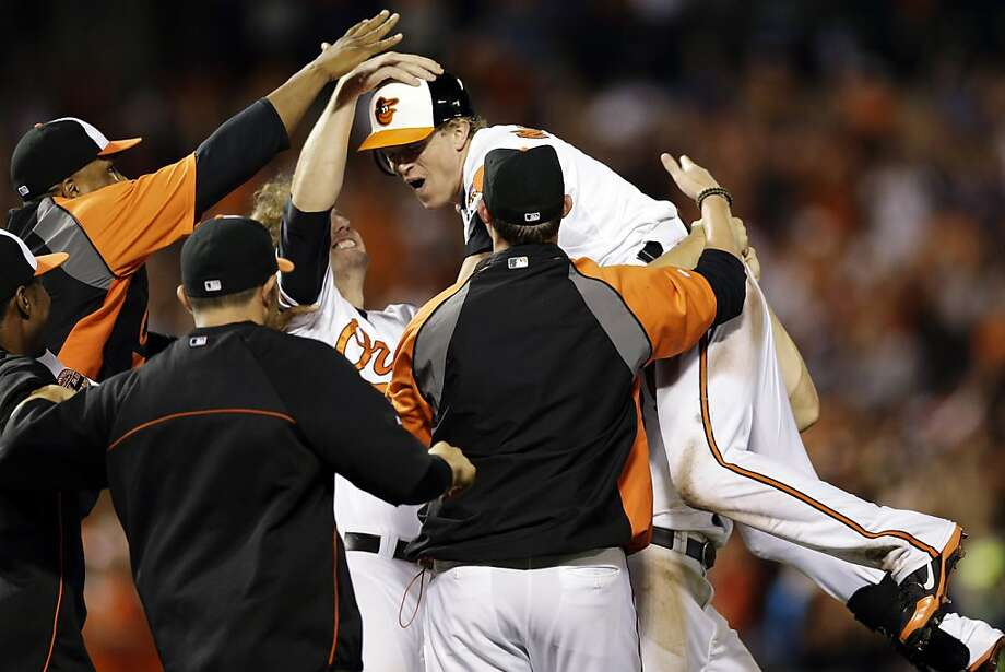 Baltimore Orioles' Nate McLouth, center, celebrates with teammates after Manny Machado scored a run on McLouth's single in the ninth inning. Photo: Patrick Semansky, Associated Press
