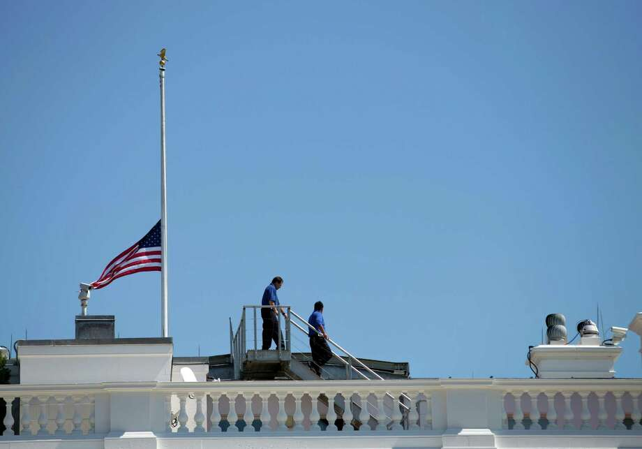 White House workers walk on the roof of the White House after lowering the flag to half staff for the death of U.S. ambassador to Libya Christopher Stevens, Wednesday, Sept. 12, 2012 in Washington.  (AP Photo/Evan Vucci) Photo: Evan Vucci