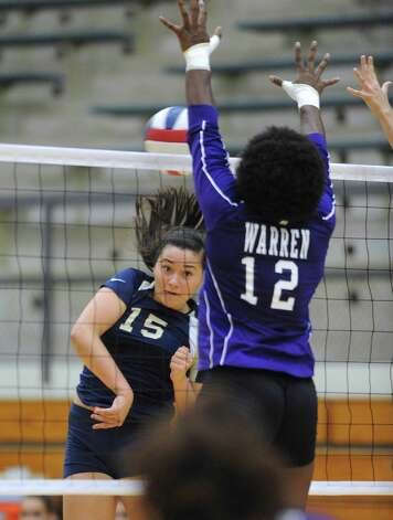 Brianna Sotello (15) of O'Connor has her spike blocked by Laycia Robinson (12) of Warren during girls volleyball action at the Taylor Fieldhouse on Wednesday, Sept. 12, 2012. Photo: Billy Calzada, San Antonio Express-News / © San Antonio Express-News