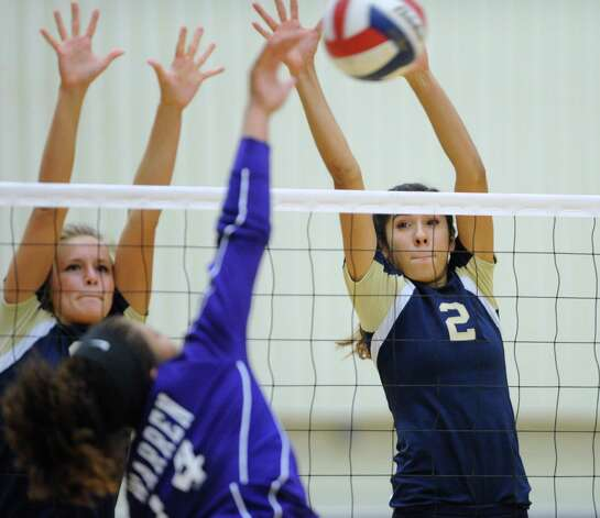 Brooke Burgess, left, and Alex Ecker of O'Connor play defense against Aaliyah Cook of Warren during girls volleyball action at the Taylor Fieldhouse on Wednesday, Sept. 12, 2012. Photo: Billy Calzada, San Antonio Express-News / © San Antonio Express-News