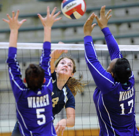 Kristin Fording of O'Connor spikes the ball as Lauren McQueen, left, and Maliya Evans of Warren defend during girls volleyball action at the Taylor Fieldhouse on Wednesday, Sept. 12, 2012. Photo: Billy Calzada, San Antonio Express-News / © San Antonio Express-News
