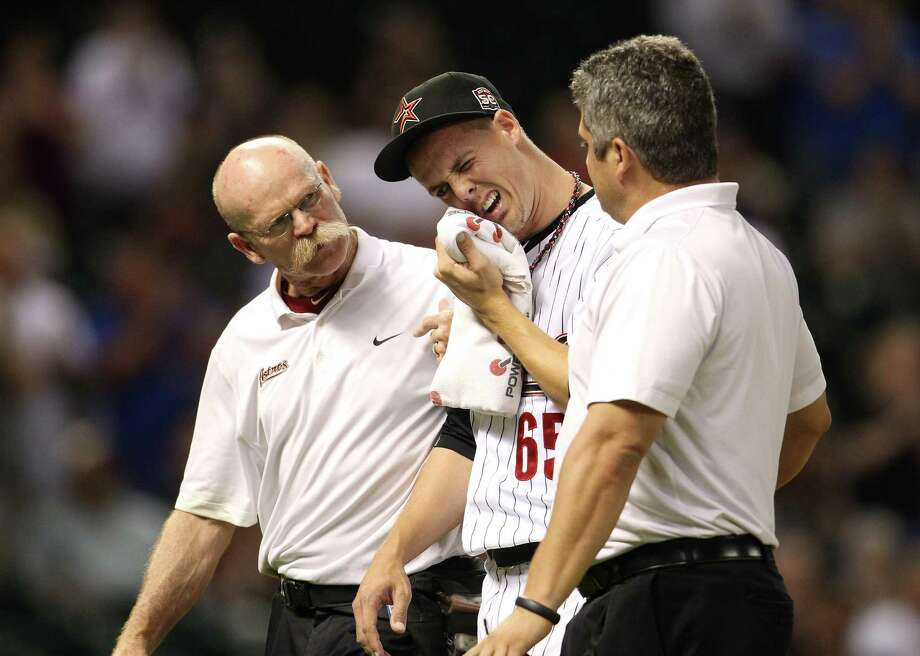 Reliever Mickey Storey is helped by assistant trainer Rex Jones, left, and head trainer Nate Lucero after suffering a bruised jaw when hit by a line drive. Photo: Karen Warren / © 2012  Houston Chronicle