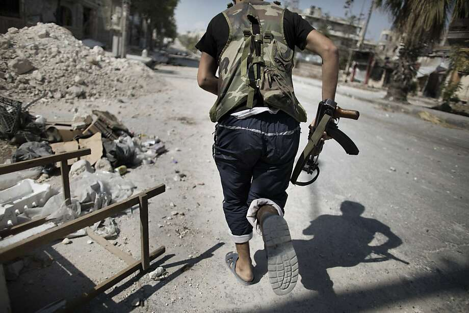 A Syrian rebel fighter runs in a sniper alley in the Saif al-Dawla neighbourhood of Aleppo on September 12, 2012. Syrian rebels have vowed to retake control of the large Hanano army base in Aleppo, a few days after loosing control of it to Syrian government forces. Photo: Marco Longari, AFP/Getty Images