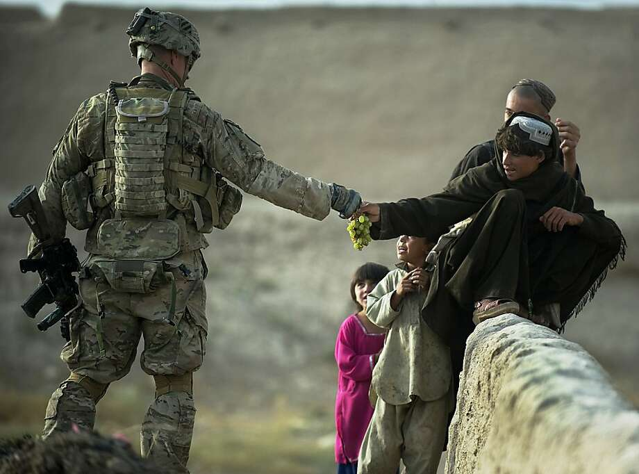 Making friends: A soldier from the 1st Platoon, Delta Coy, 1-64  AR of the U.S. Army shares grapes with boys from the local Pashtu tribe  near Kandahar Air Field, Afghanistan. Photo: Tony Karumba, AFP/Getty Images