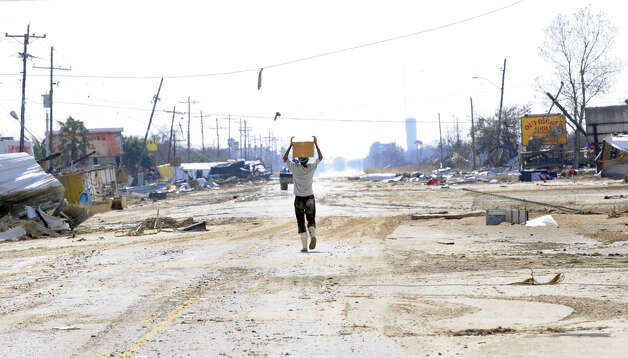 A man carries a case of MRE's down what remains of Texas 87 at Crystal Beach after Hurricane Ike.  Enterprises file photo / Beaumont
