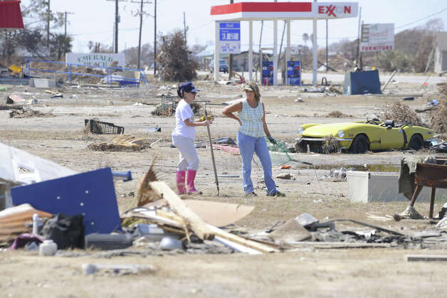 Janet Cox, left, and Kim Barksdale search through surge debris at Crystal Beach for any signs of their possessions after their homes were destroyed by Hurricane Ike. Enterprise file photo / Beaumont