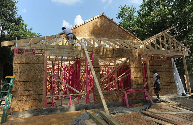 A construction crew works on a home that is being rebuilt and refortified with new building technology after Hurricane Ike destroyed the structure. Guiseppe Barranco/The Enterprise
