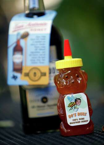 "A bottle of Bo DeWeese's ""Bo's Bees"" honey stands Sept. 5, 2012 in front of a bottle of Deep Eddy's Sweet Tea Vodka. DeWeese was told by his dad he could have a bike if he bought it himself. Just like his father before him, Edward gave his 9-year-old son a bee hive to sell the honey for money. Bo's honey is now in high demand, as the makers of Deep Eddy's Sweet Tea Vodka out of Austin have sampled his honey and think it's the best in Texas. Photo: William Luther, San Antonio Express-News / © 2012 San Antonio Express-News"