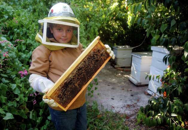 Bo DeWeese, seen Sept. 5, 2012, was told by his dad he could have a bike if he bought it himself. Just like his father before him, Edward gave his 9-year-old son a bee hive to sell the honey for money. Bo's honey is now in high demand, as the makers of Deep Eddy's Sweet Tea Vodka out of Austin have sampled his honey and think it's the best in Texas. Photo: William Luther, San Antonio Express-News / © 2012 San Antonio Express-News
