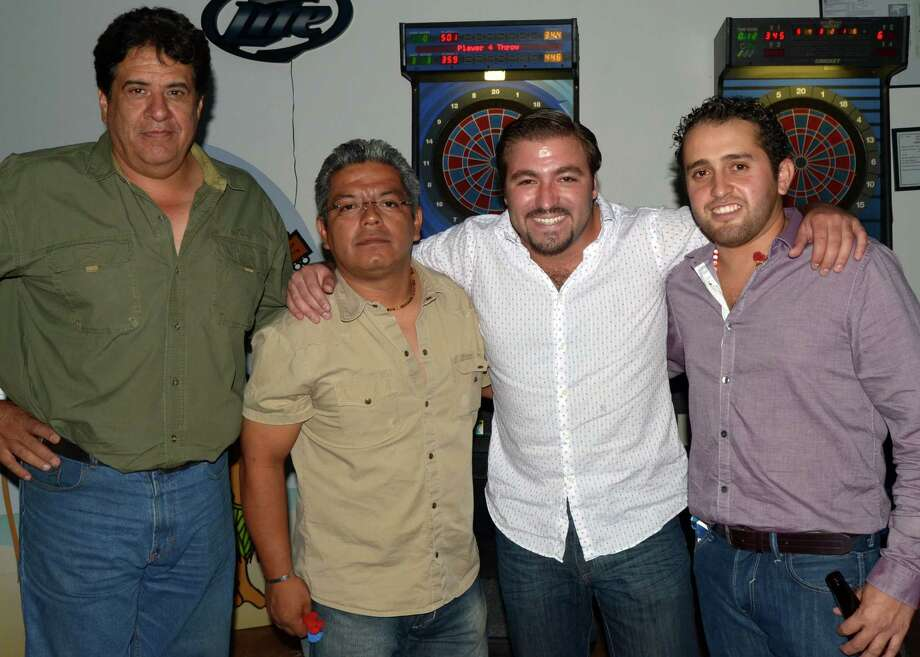 Buddies Juan Luis Guerra (from left), Poncho Aureilo (cq), Luis Miguel and Leonardo Miguel have a night of darts at Coco Bongo on September 7, 2012. Robin Johnson