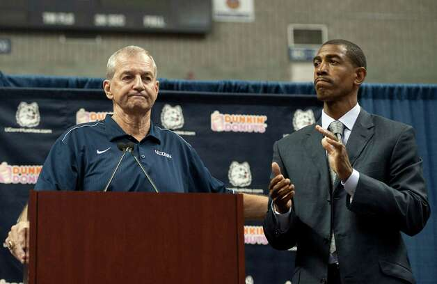 Connecticut head coach Jim Calhoun, left, reaches out to as Kevin Ollie, right, during a news conference announcing Calhoun's retirement, Thursday, Sept. 13, 2012,  in Storrs, Conn. Ollie, an assistant coach under Calhoun, will succeed him. Photo: Jessica Hill, Jessica Hill/Associated Press / Associated Press