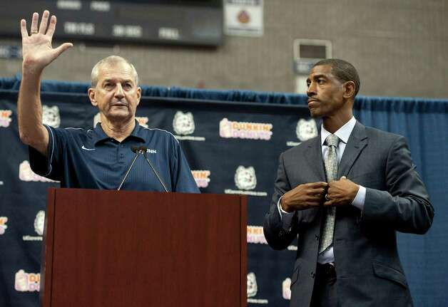 Connecticut head coach Jim Calhoun, left, gestures as Kevin Ollie, right, looks on during a news conference announcing Calhoun's retirement, Thursday, Sept. 13, 2012,  in Storrs, Conn. Ollie, an assistant coach under Calhoun, will succed him. Photo: Jessica Hill, Jessica Hill/Associated Press / Associated Press