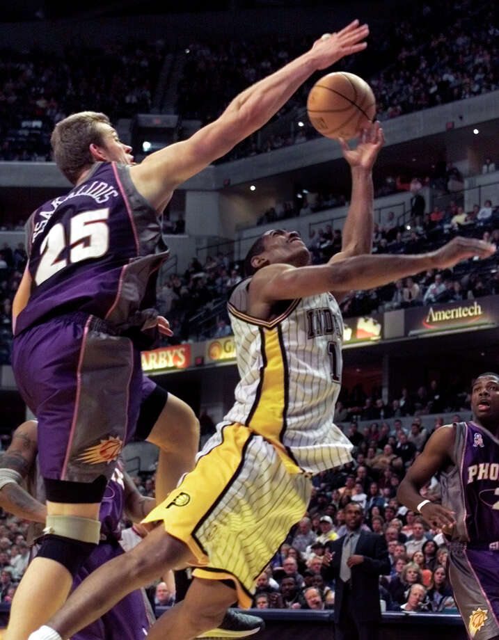 Phoenix Suns center Jake Tsakalidis (25) comes from behind Indiana Pacers guard Kevin Ollie to block a shot in the fourth quarter in Indianapolis, Friday, April 5, 2002. The Pacers defeated the Suns 97-87. Photo: MICHAEL CONROY, (AP Photo/Michael Conroy) / Associated Press