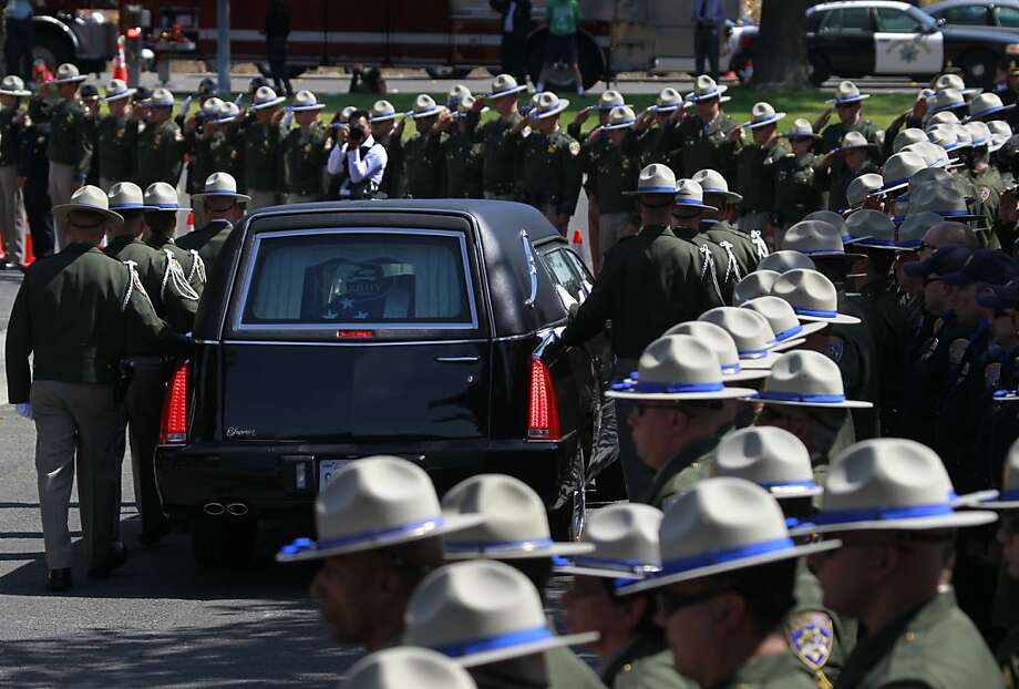 CHP officers stand at attention as Kenyon Youngstrom's funeral procession passes Thursday in Vacaville. Photo: Paul Chinn, The Chronicle