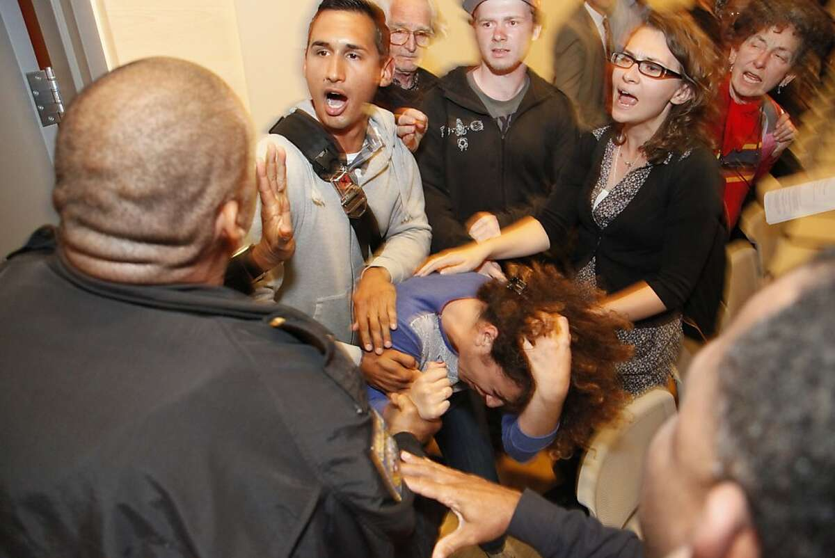 Lalo Gonzalez tries to protect Ali Oligny from being dragged out of the CCSF Board of Trustees meeting by police on Tuesday, Sept. 11, 2012 at the City College of San Francisco's chinatown campus. The board of trustees is leaning towards asking the state for a special trustee to help them preserve their accreditation which many they loudly opposed. Gonzalez is a graduate of San Francisco State University and Oligny is currently UC Berkeley student.