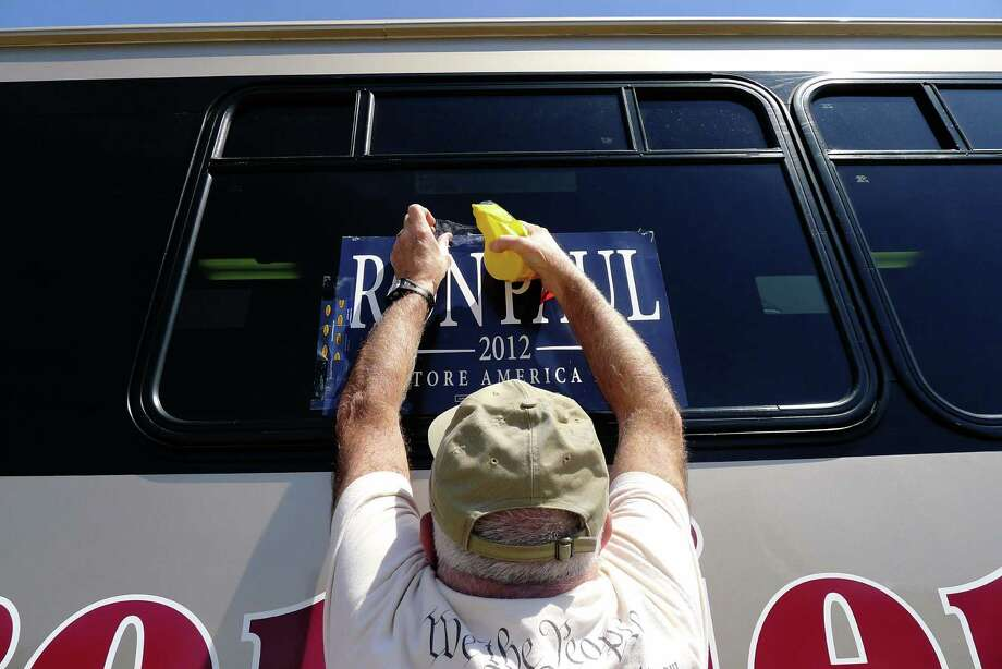 Ron Paul for president supporter Mike Kelly of Selkirk tapes a sign on the bus going to Cornell University from UAlbany in Albany N.Y. Thursday April 19, 2012. Photo: Michael P. Farrell, Albany Times Union / ONLINE_YES