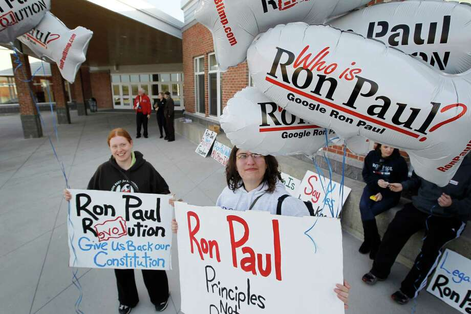 Breanna Wentworth, from Colchester, Conn., left, and Samantha Hart from Norwich, Conn., campaign for Republican presidential candidate Ron Paul before his son, Sen. Rand Paul, R-Ky., arrives to campaign for his father at Windham High School in Windham, N.H., Saturday, Jan. 7, 2012. Photo: Charles Dharapak, Associated Press / AP