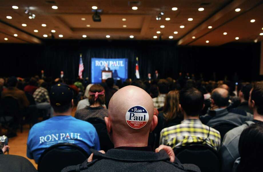 A Ron Paul supporter wears a sticker on his head as Paul speaks at Colorado State University in Fort Collins, Colo., Tuesday, Jan. 31, 2012. Photo: Chris Schneider, Associated Press / FR170036 AP