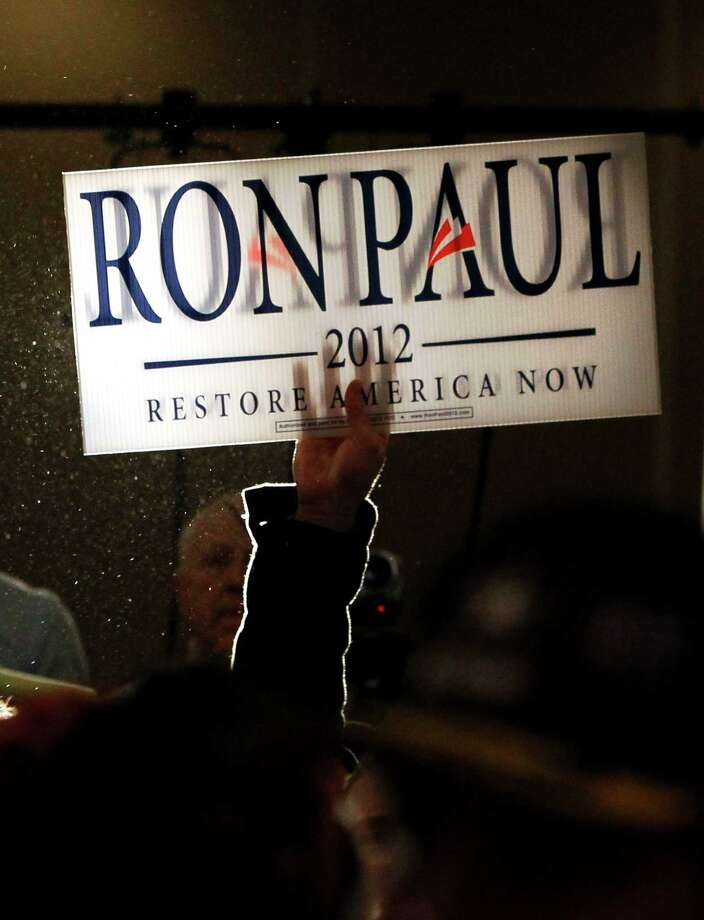 A supporter of Ron Paul holds up a sign during the North Dakota caucus Tuesday, March 6, 2012 in Fargo, N.D. Photo: Charles Rex Arbogast, Associated Press / AP