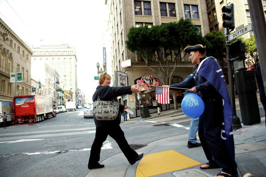 John Sharkey (right), of San Francisco, hands out pamphlets on Ron Paul outside of the Marriott Hotel on Thursday, April 5, 2011 in San Francisco, Calif. Photo: Beck Diefenbach, Special To The Chronicle / ONLINE_YES