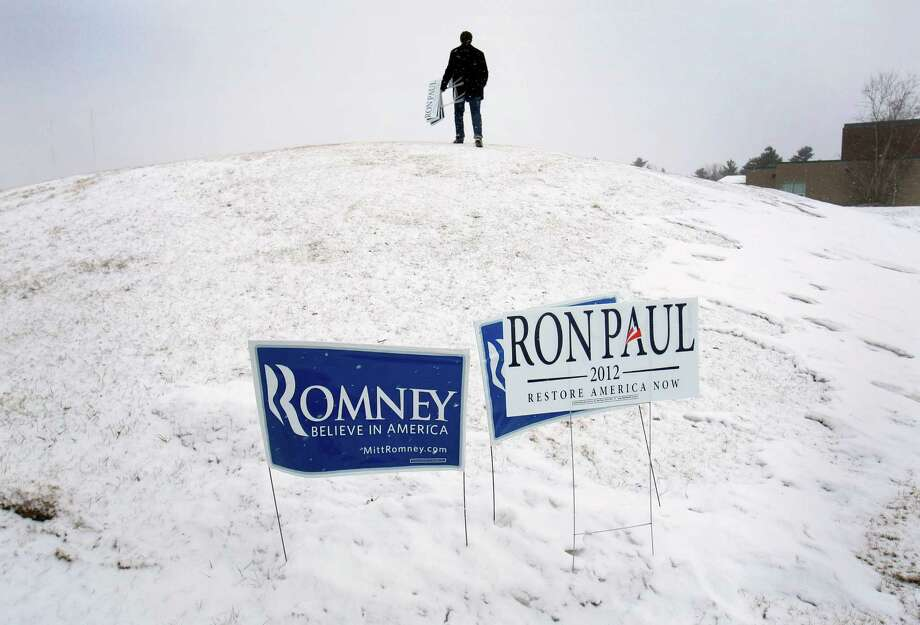Mike Donahue climbs a snowy hill to plant signs in support of Ron Paul outside a caucus, Saturday, Feb. 11, 2012, in Portland, Maine. Photo: Robert F. Bukaty, Associated Press / AP