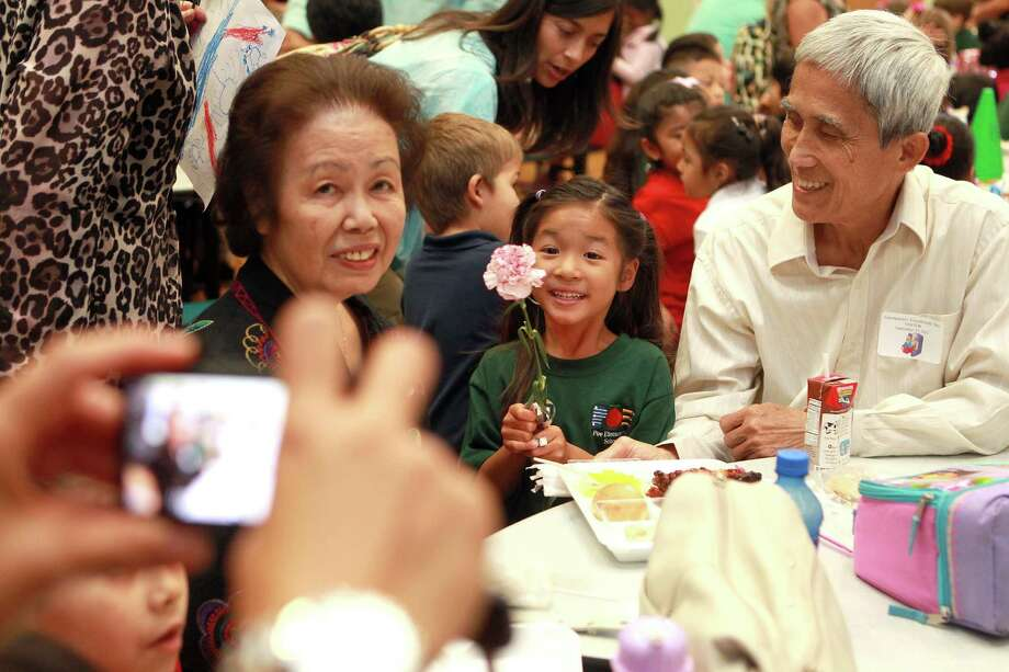Grace Hau, 5, had her picture taken with her grandmother, Macsuu Hau, and grandfather, Hue Phan, as they ate lunch together during Poe Elementary School's grandparents day Thursday, Sept. 13. 