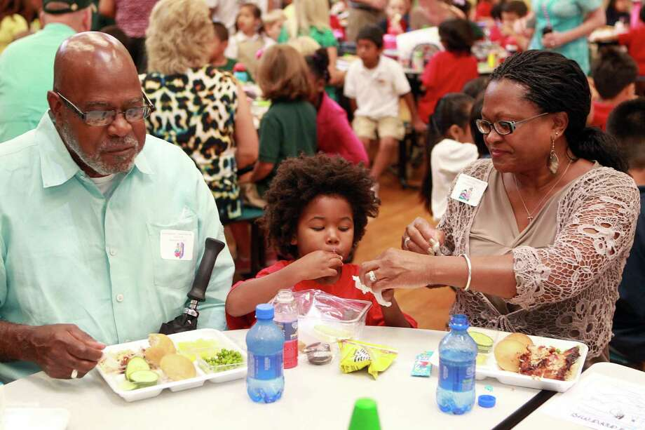Kindergartner Ekavu Ashe, 5, ate lunch with his grandparents Michael and Fredricka Perry during Poe Elementary School's grandparents day Thursday, Sept. 13.  Photo: Johnny Hanson, Houston Chronicle / © 2012  Houston Chronicle