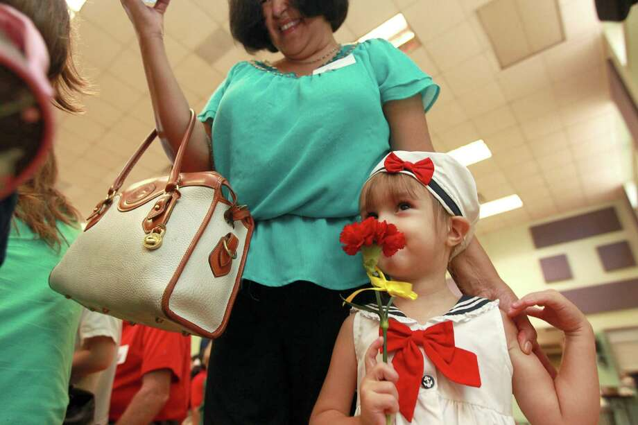 Rebekah Heiner, 3, smells a flower that her grandmother Delfa Wyeth was given. They visited her brother, Patrick Heiner, at Poe Elementary School during the school's grandparents day Thursday, Sept. 13. Photo: Johnny Hanson, Houston Chronicle / © 2012  Houston Chronicle