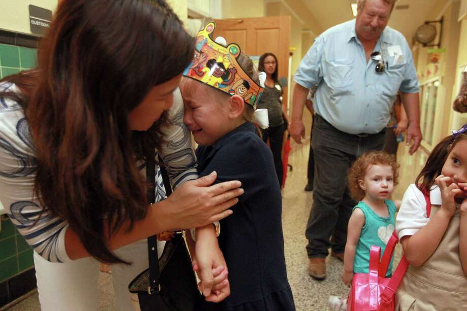 Lia Rowell, 6, holds onto the arm of her mother, Lesli Rowell, after she first said goodbye to her grandmother and then did not want to say goodbye to her mother after they visited the kindergartner for lunch at Poe Elementary School during the school's grandparents day Thursday, Sept. 13, 2012, in Houston. 