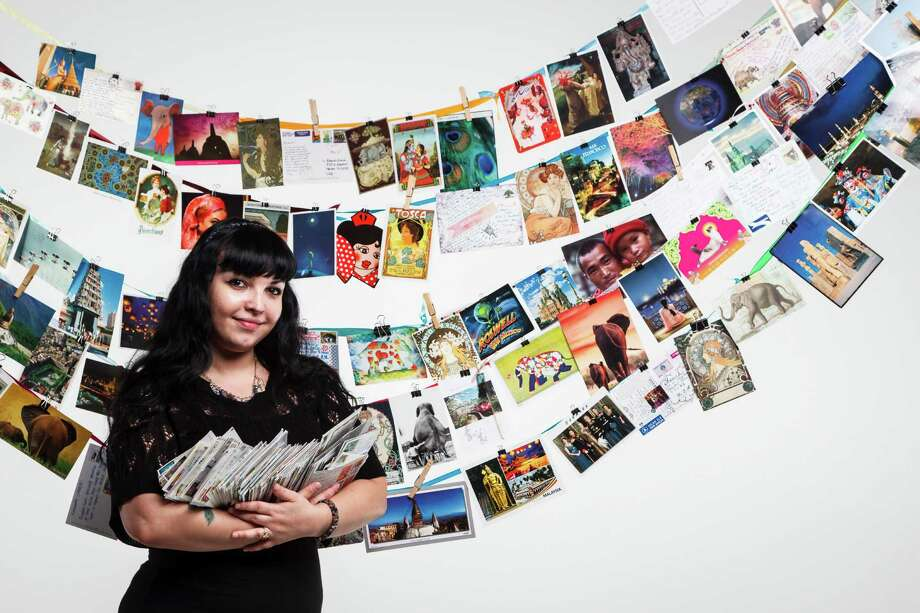 Amanda Andriola, 25, has joined the website Postcrossing and exchanges postcards from people all over the world amassing more than 900 postcards. Photo: Michael Paulsen / © 2012 Houston Chronicle