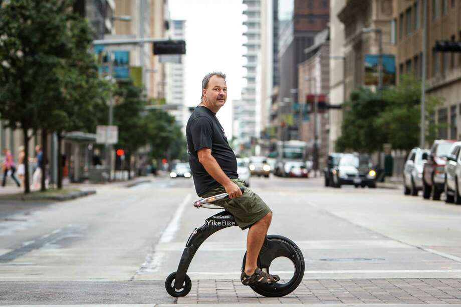 Jimmy Cox rides his YikeBike through downtown, Thursday, Sept. 13, 2012, in Houston.  The electric bicycle weighs 22lbs. and folds down to the size of a medium package to be carried around.  ( Michael Paulsen / Houston Chronicle ) Photo: Michael Paulsen / © 2012 Houston Chronicle