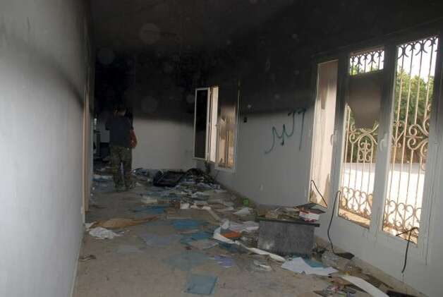 "A man walks through a room in the gutted U.S. consulate in Benghazi, Libya, after an attack that killed four Americans, including Ambassador Chris Stevens, Wednesday, Sept. 12, 2012. The American ambassador to Libya and three other Americans were killed when a mob of protesters and gunmen overwhelmed the U.S. Consulate in Benghazi, setting fire to it in outrage over a film that ridicules Islam's Prophet Muhammad. Ambassador Chris Stevens, 52, died as he and a group of embassy employees went to the consulate to try to evacuate staff as a crowd of hundreds attacked the consulate Tuesday evening, many of them firing machine-guns and rocket-propelled grenades. Partial graffiti reads, ""akbar,"" Arabic for ""great."" (Ibrahim Alaguri / Associated Press)"