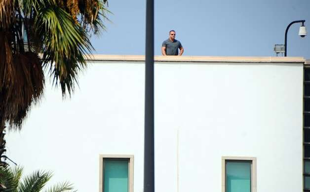 A man stands atop the United States embassy in Tunis, Wednesday, Sept.12, 2012 as ultraconservative Muslims demonstrate outside the embassy to demand the closure of the embassy and the departure of the ambassador. The American embassies in Algeria and Tunisia warned of more protests Wednesday, following attacks by protesters in neighboring Libya in which the U.S. ambassador and three embassy staff were killed. (Hassene Dridi / Associated Press)
