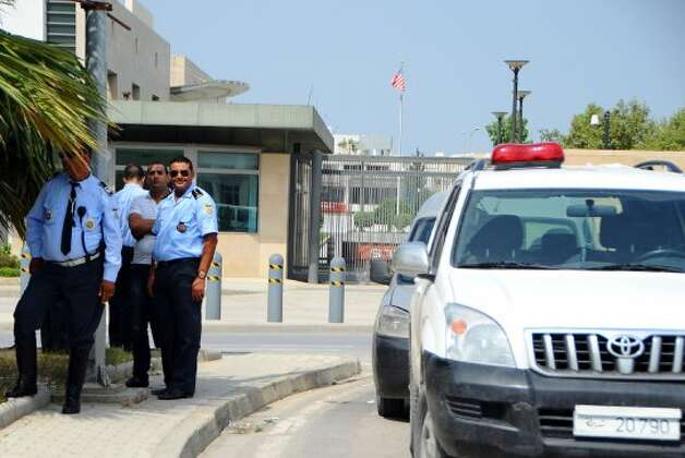 Police officers guard the United States embassy in Tunis, Wednesday, Sept.12, 2012 as ultraconservative Muslims demonstrate outside the embassy to demand the closure of the embassy and the departure of the ambassador. The American embassies in Algeria and Tunisia warned of more protests Wednesday, following attacks by protesters in neighboring Libya in which the U.S. ambassador and three embassy staff were killed. (Hassene Dridi / Associated Press)