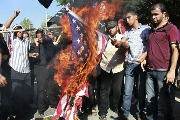 "Palestinians burn a U.S. flag during a protest against the movie, ""Innocence of Muslims,"" near the United Nations office in Gaza City, Wednesday, Sept. 12, 2012. Muslim anger over perceived Western insults to Islam has exploded several times, most recently in Tuesday's attacks against U.S. diplomatic posts in the Middle East in which U.S. ambassador to Libya Chris Stevens and three other Americans were killed. (Adel Hana / Associated Press)"