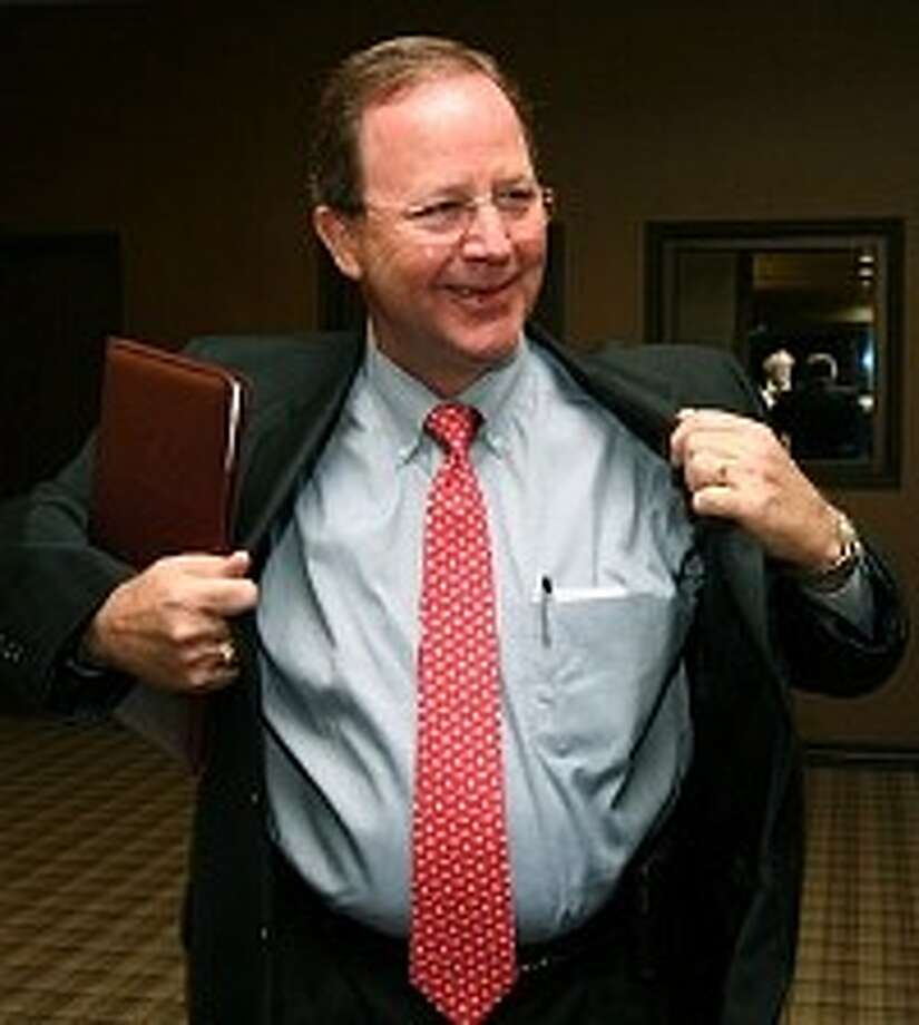 Republican Bill Flores puts on his coat before watching election results in Bryan. Photo: AP