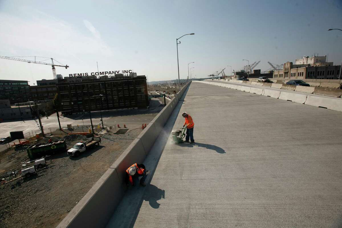 A work crew prepares the new northbound state Route 99 on Thursday just days before the new section of highway is scheduled to open through Seattle's Sodo neighborhood. It is scheduled to open on Monday.