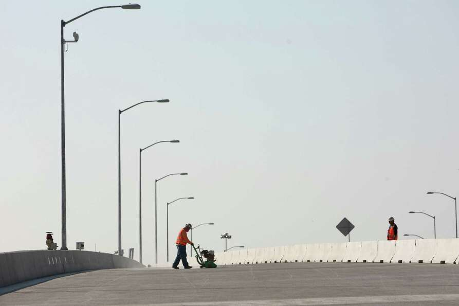 A work crew prepares the new northbound state Route 99 on Thursday, just days before the new section