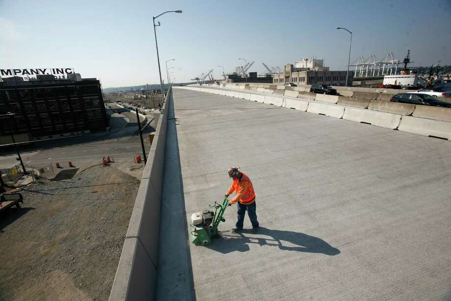 A work crew prepares the new northbound state Route 99 on Thursday, just days before the new section of highway is scheduled to open through Seattle's Sodo neighborhood. It is scheduled to open on Monday. Photo: JOSHUA TRUJILLO / SEATTLEPI.COM