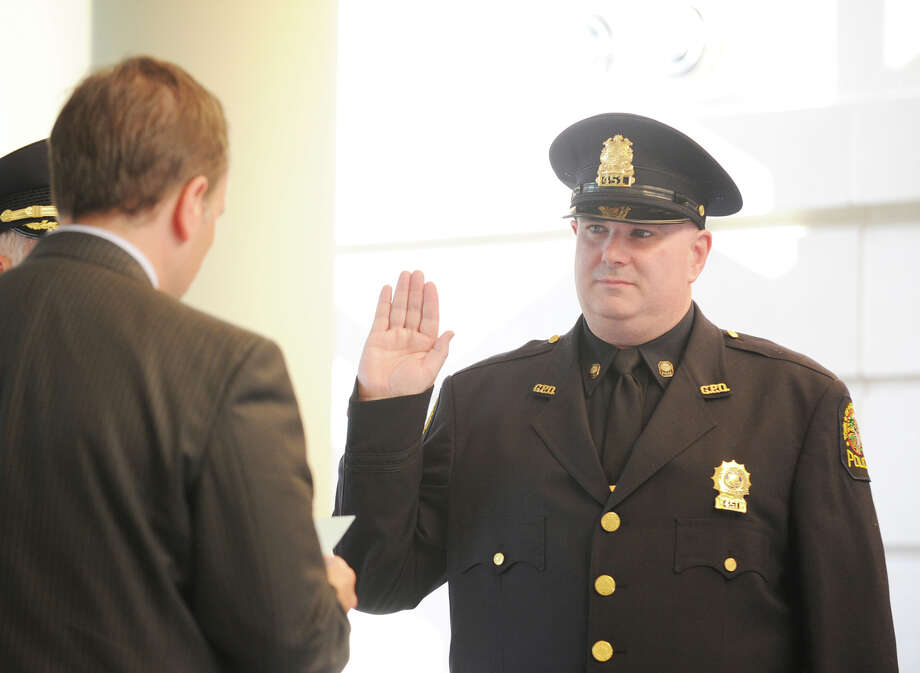 Greenwich First Selectman Peter Tesei, left, swears in Greenwich Police Officer Patrick Smyth as a sergeant during a promotion ceremony for Smyth at Greenwich Police Headquarters, Thursday, Sept. 13, 2012. Photo: Bob Luckey / Greenwich Time