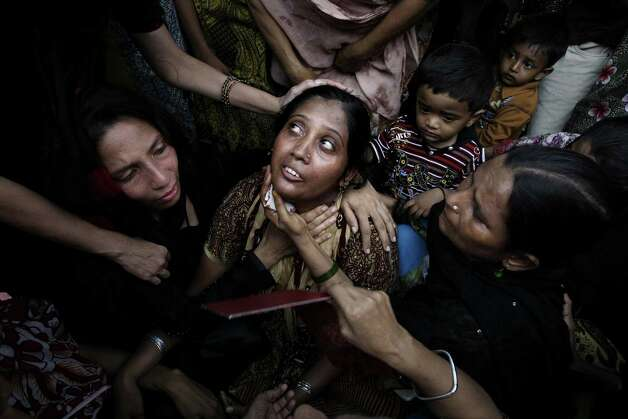 People comfort a woman who lost a family member in a garment factory fire, during a funeral in Karachi, Pakistan, Thursday, Sept. 13, 2012. Pakistani police say they have registered a murder case against the owners and managers of a garment factory in the southern city of Karachi where a fire killed hundreds of people. Photo: Fareed Khan, Associated Press / AP