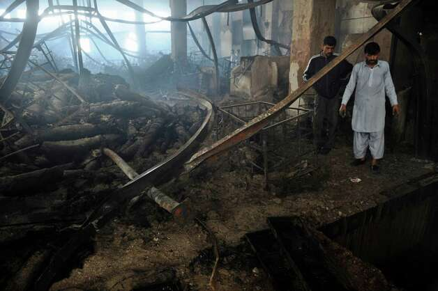 Pakistan people gather in a garment factory following a fire in which at least 289 people died in Karachi on September 13, 2012, on the third day of the fire incident.   Police in Karachi have registered a murder case against the owners of a garment factory where a fire killed at least 289 people in the country's worst ever industrial disaster, officers said. Photo: RIZWAN TABASSUM, AFP/Getty Images / AFP