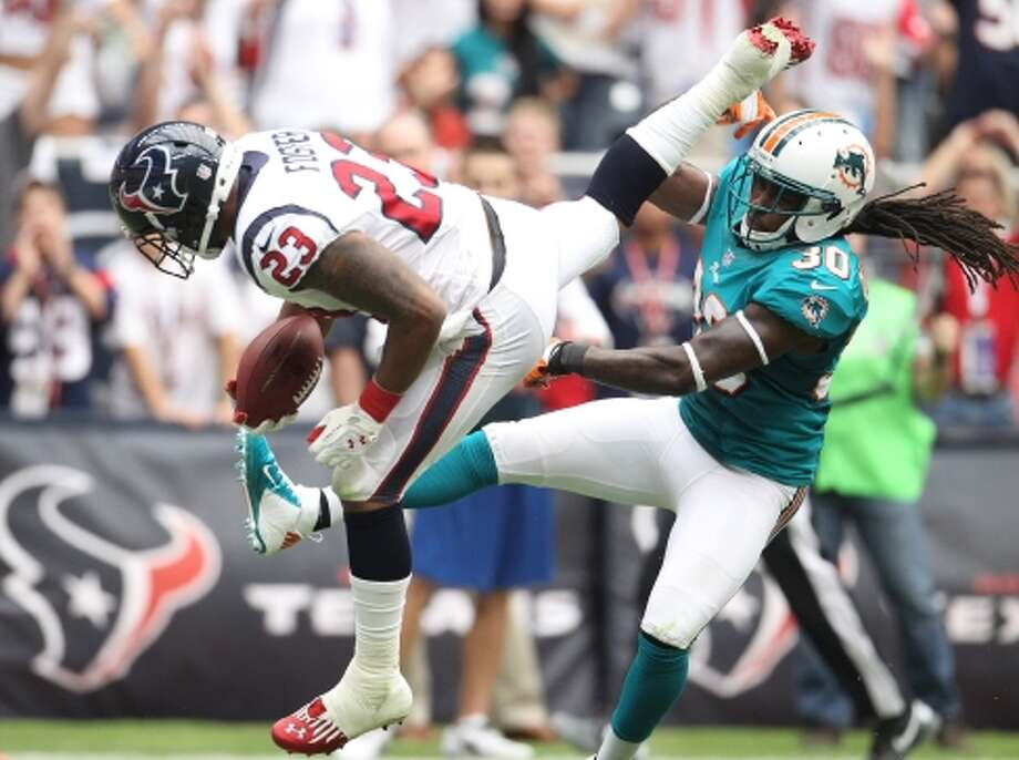 Houston Texans running back Arian Foster leaps past Miami Dolphins defensive back Chris Clemons for a touchdown during the second quarter. (Karen Warren / Houston Chronicle)