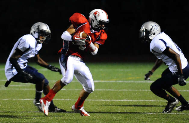 Foran's #2 Nicholas Weissauer completes a pass just as two Hillhouse players converge to tackle, during boys football action in Milford, Conn. on Thursday September 13, 2012. Photo: Christian Abraham / Connecticut Post