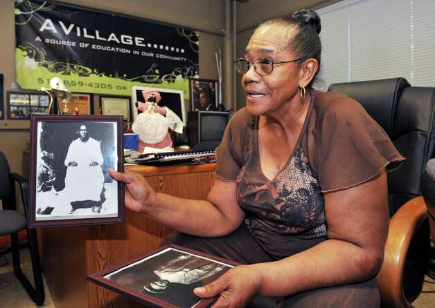 A Village organizer Clara Phillips holds photographs of her grandparents as she recalls growing up in the south and plans for Saturday's  Mississippi Day Celebration in Albany Thursday Sept. 13, 2012.  (John Carl D'Annibale / Times Union) Photo: John Carl D'Annibale / 00019245A