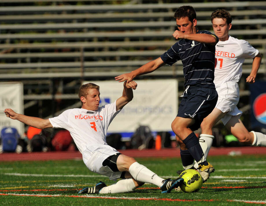 Ridgefield defender Travis Leiter clears the ball away from Staples' Joe Greenwald during their game at Ridgefield High School on Thursday, Sept. 13, 2012. Ridgefield won, 2-1. Photo: Jason Rearick / The News-Times