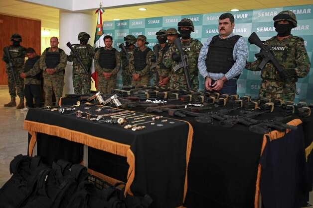 Mexican marines in face masks flank Jorge Costilla Sanchez and other suspects dressed in military fatigues, who are believed to be his bodyguards. Photo: Dario Lopez-Mills, Associated Press / AP
