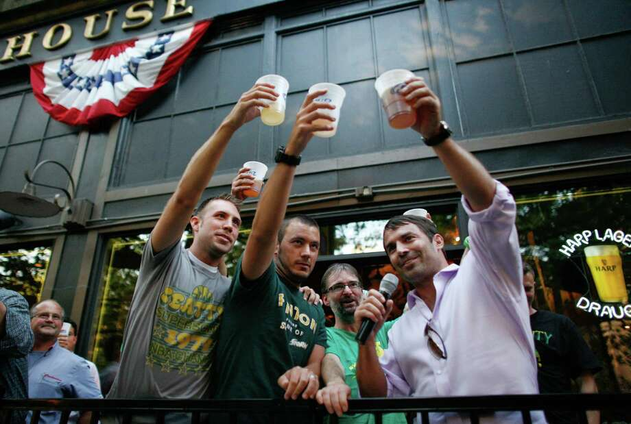 Ricky Oliver, left, and Colin Hughes join arena investor Chris Hansen, right, during a toast at FX McRory's in the Pioneer Square neighborhood on Thursday, Sept. 13, 2012. Hansen bought a round of beers for arena supporters after the Seattle City Council voted to approve his arena proposal. Photo: JOSHUA TRUJILLO / SEATTLEPI.COM